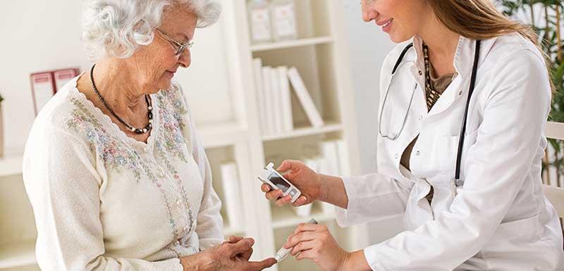 Médecin contrôlant la glycémie d'une femme agée