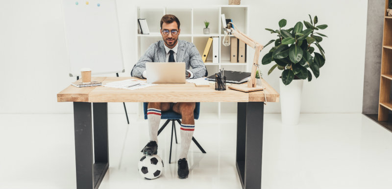 homme au bureau avec un ballon de foot dans les pieds