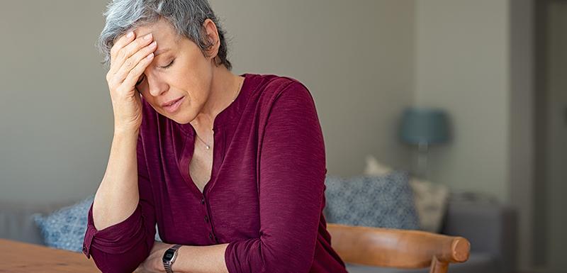 Femme âgée ayant une migraine et se tenant la tête