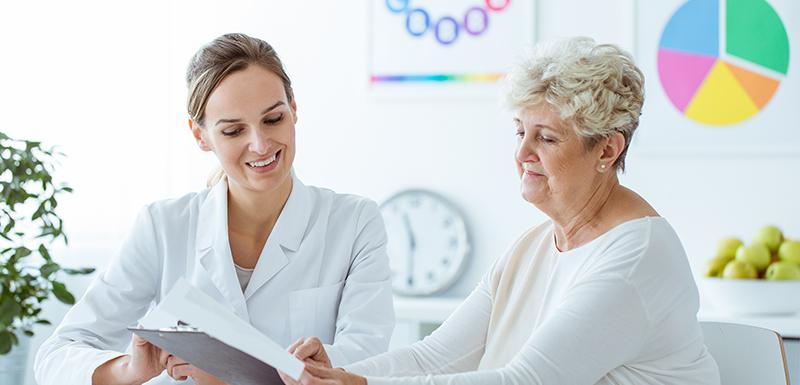nutritionniste montrant un plan d'alimentation à une personne âgé pour éviter l'hyper-insulinémie