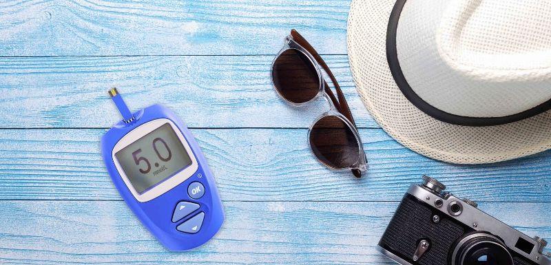 capteur de glycémie sur une table, avec accesoires de vacances à côté